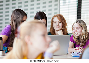 Four female college students working on their homework