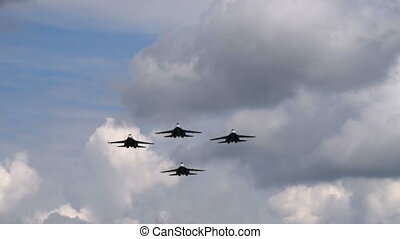 Four fighter planes flying overhead