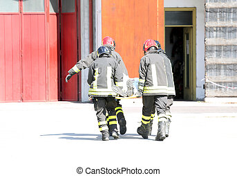four firefighters in action carry a stretcher with injured