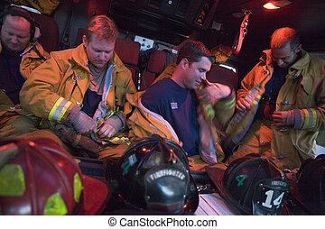 Four firemen in fire engine putting on gear (blur)