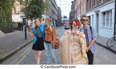 Four friends are walking the streets of London. Do selfies, laugh and fool around. On summer vacation.