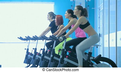 Four friends athletes pedaling on a stationary bike at the gym show thumbs up