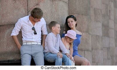 Four friends boys with girls sit and talk near colonnade