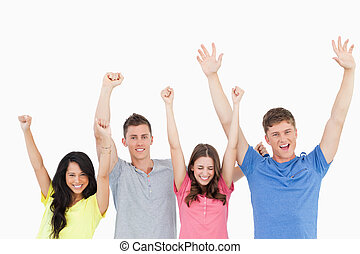 Four friends celebrating together with their hands in the air as they all look at the camera