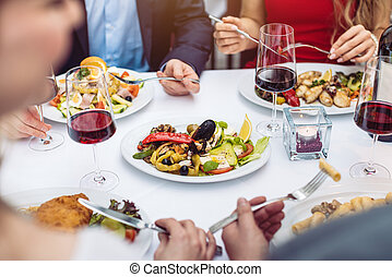 Four friends eating Italian food in fancy restaurant, close-up