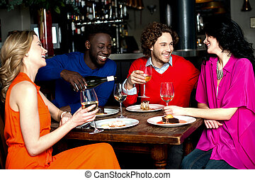 Four friends enjoying dinner at a restaurant - Friends...