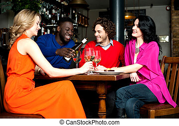 Four friends enjoying dinner at a restaurant