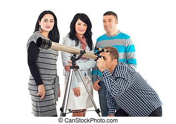 Four friends having fun with telescope