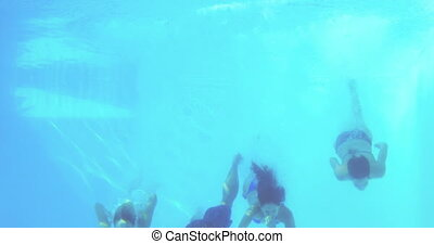 Four friends jumping into swimming