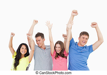 Four friends party together with hands in the air