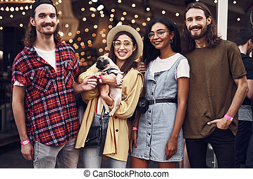 Four friends smiling and posing for photo with cute puppy - ...