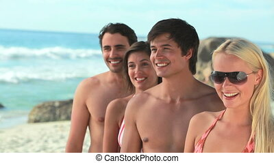 Four friends smiling and posing in a line while at the beach