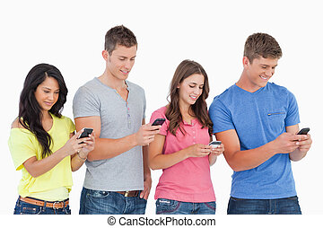 Four friends standing to the side slightly sending texts