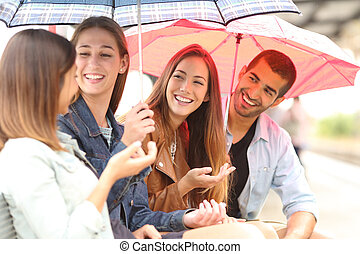 Four friends talking outdoor in a rainy day