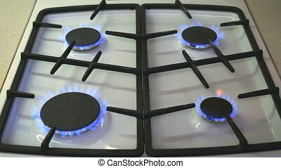 Four gas burners burn blue flame on a gas stove
