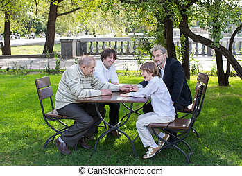 Four generations of men sitting at a wooden table in a park, laughing and talking