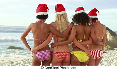 Four girls embracing each other while wearing santa hats