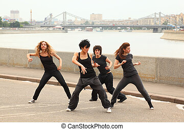 Four girls in same black clothes dancing on embankment on...