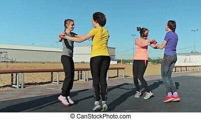 Four girls train - jumping exercise