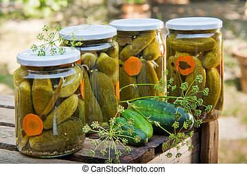 Four glasses of pickled cucumbers in the garden