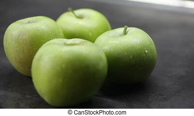 Green apples lie on the table in the kitchen