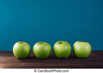 Four green apples on brown wooden background.
