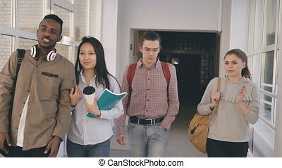 Four groupmates of different ethnicity are walking in long...