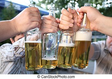 four hands with the bottles of the beer