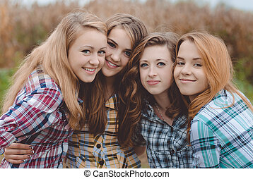 Four happy smiling amazing teenage girls having fun together