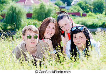 Four happy smiling teen friends in green grass