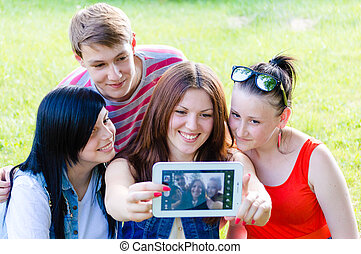 Four happy teen friends taking picture of themselves with tablet