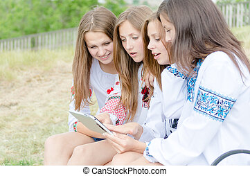 Four happy teen girl friends and tablet computer