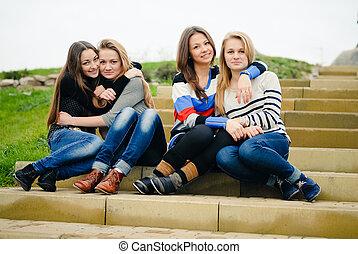Four happy teen girls friends having fun outdoors