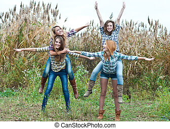 Four happy teen girls friends having fun outdoors