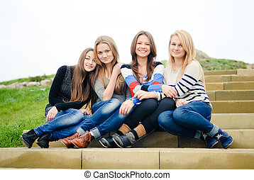 Four happy teen girls friends hugging and having fun...