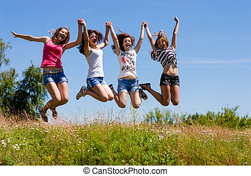 Four happy teen girls friends jumping high against blue sky...