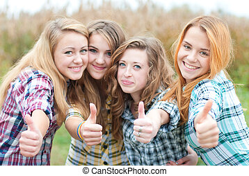 Four happy teen girls friends showing okay