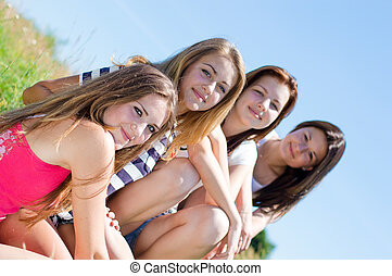Four happy teen girls sitting together against blue sky