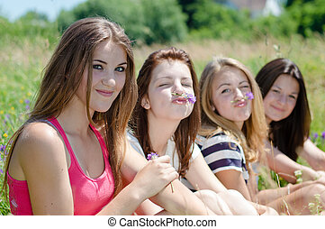 Four happy teen girls sitting together on green lawn