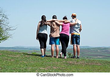 Four happy teenage friends embracing on blue sky background