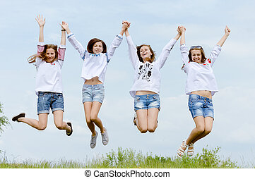 Four happy teenage friends jumping high in blue sky