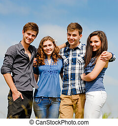 Four happy teenage friends outdoors