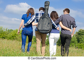 Four happy teenage friends walking together outdoors