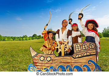 Four kids in pirate costumes behind ship
