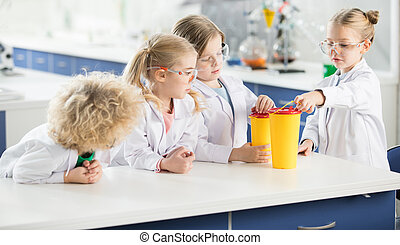 Four kids in science laboratory making experiment