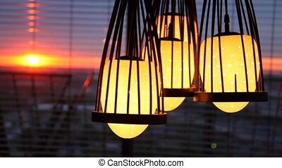 Four lamps hang before jalousie where sunset is visible -...