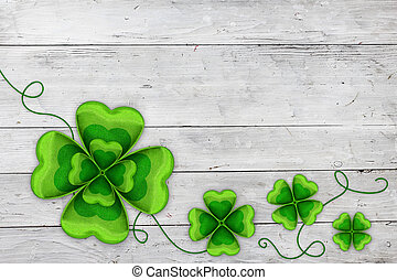 Four clovers on white wooden banner. Celebrating St Patricks day on March 17th. Traditional symbol of luck, happiness and wealth.