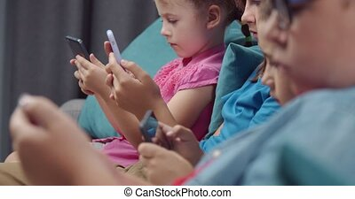 Four little friends playing on own smartphones in silence - ...