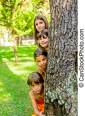 Four little girls  peeking from behind the tree