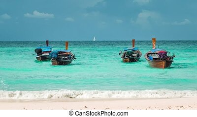 Four long-tailed boat swinging in blue waves on Bundhaya beach, and white sail boat on the horizon, Koh Lipe Thailand